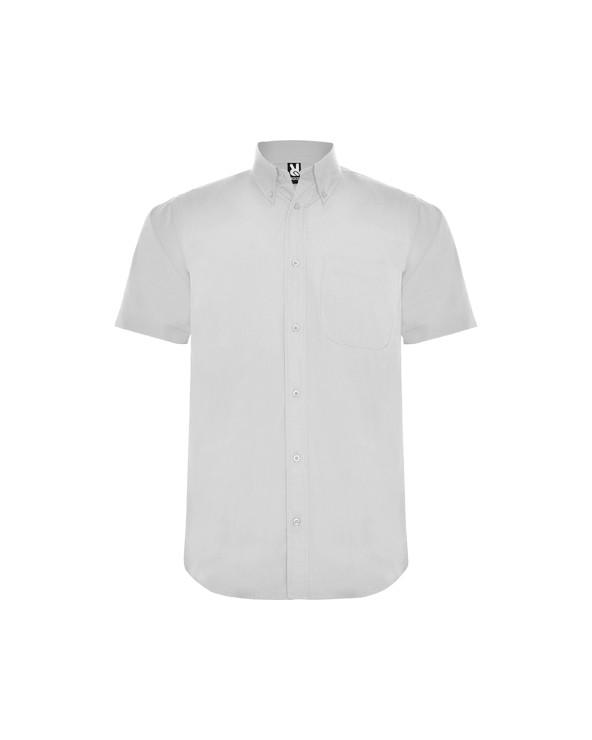 Camisa de manga corta y cuello clásico almidonado de 1 botón. Bolsillo frontal izquierdo, tapeta con 7 botones a tono y bajo co